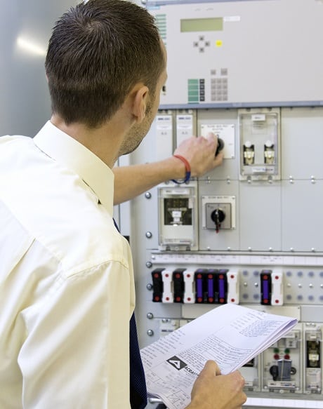 Design Engineer inspecting a protection panel with drawing